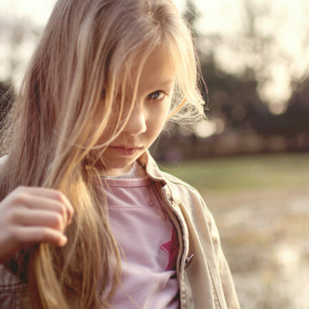 Little girl with long hair, holding a strand of hair in her hand and looking shyly at the camera.