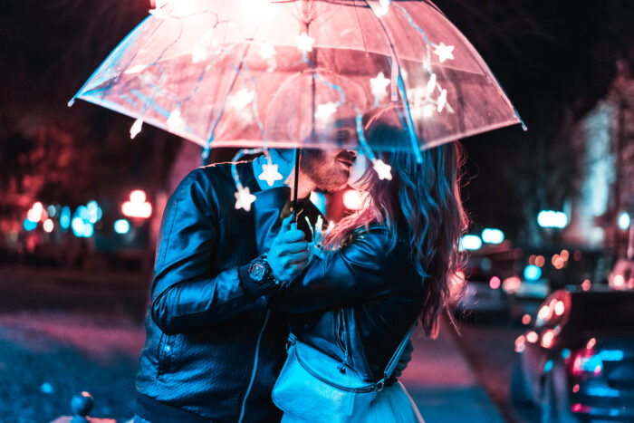 Guy and girl kissing under an umbrella on a night street